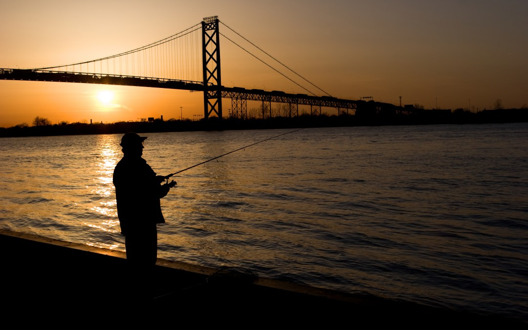 A silhouette of a person fishing at sunset with a bridge behind them.