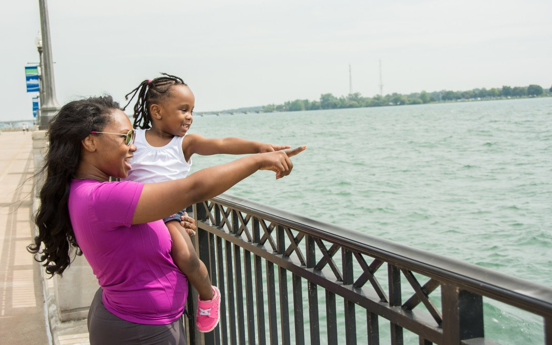 An adult and child point out over the water from a boardwalk