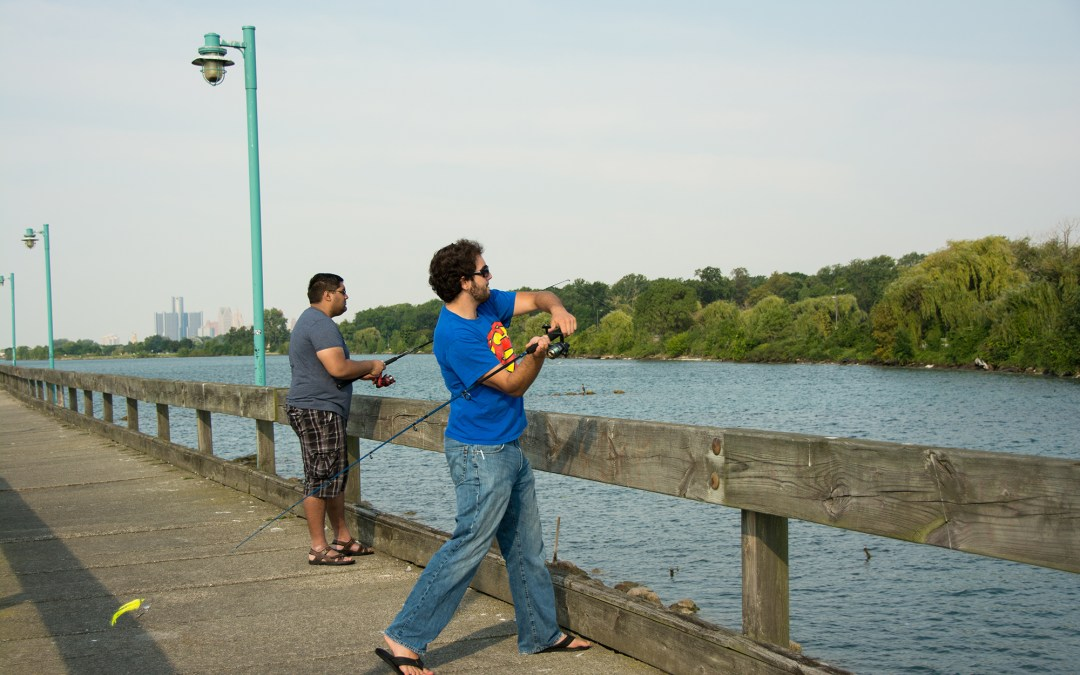 Two people fish off of a wooden pier.
