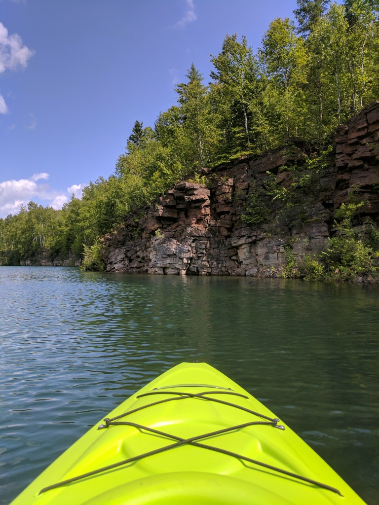 A kayak on the Great Lakes with a view of the shoreline