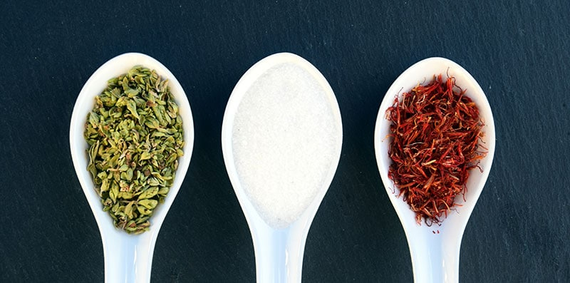 three spices lined up on white spoons against a dark background
