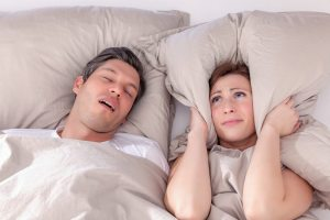 couple sleeping with man snoring and woman covering her ears