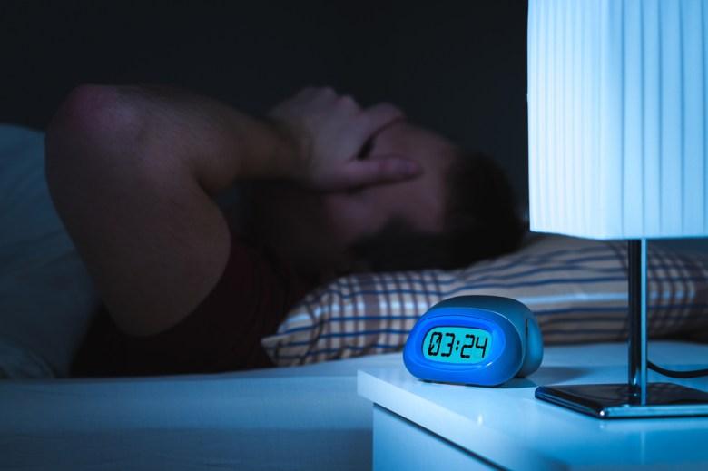Man lying in bed awake