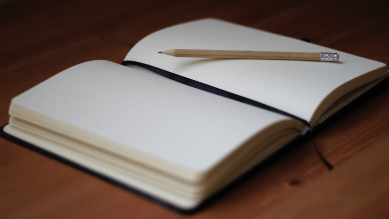 A diary and a pencil lying on a desk.