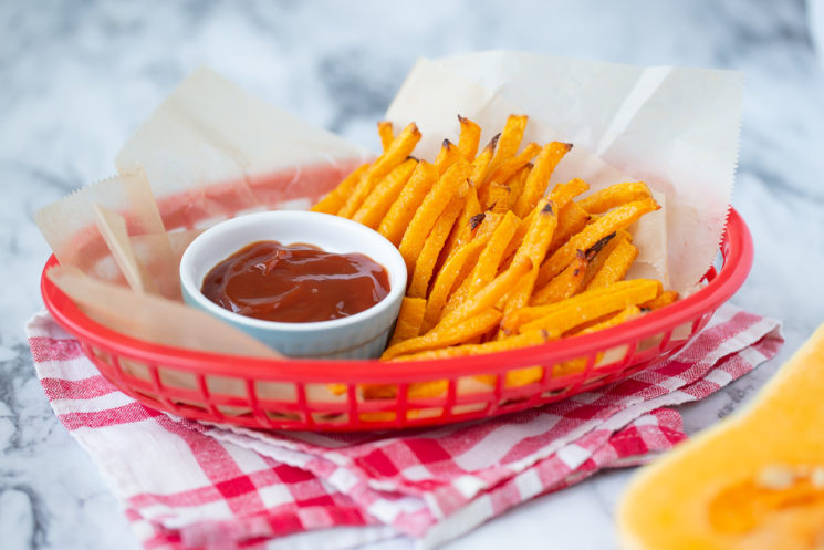 a basket of butternut squash fries with a ramekin of ketchup