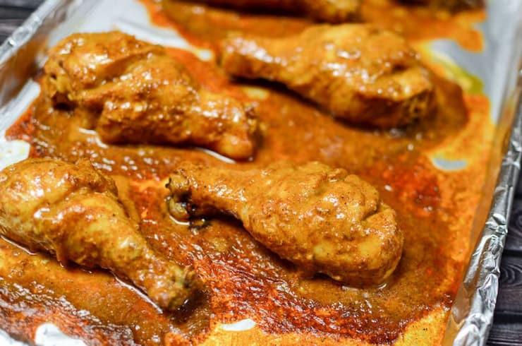 Chicken tandoori cooking on a baking sheet