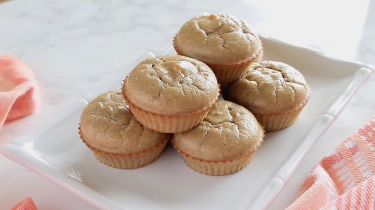 six applesauce muffins on a white plate