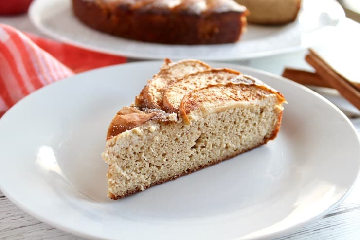 Slice of apple cake on white plate with entire cake in background next to cinnamon sticks and red and white plaid dish towel