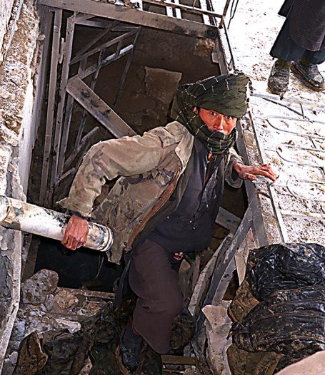 Worker bringing coats up from the Qala-i-Jhangi basement
