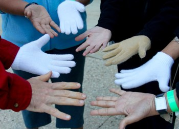 "Photo showing eight hands with varied skin tones: 4 with gloves, 4 without. By sharing three sets of ""emergency gloves"" among the five of us, we found a way to share in the warmth: each of us with one hand covered, one uncovered. Together, we created some warmth, much laughter, and good memories that remind me still today that we need solutions for solidarity and mutual support. Together, we can create warmth, even in chilly conditions."