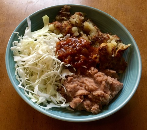 Blue bowl with refried beans in the front, shredded cabbage to the left, fried potatoes to the right, and red salsa on top, in the middle.