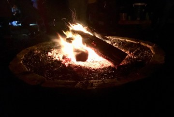 In the center of this photo is a fire pit with fire alight and bright on a dark summer night.