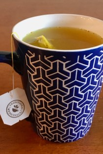 "View into blue and white patterned mug with wellness tonic on the inside and tea label ""Traditional Medicinals"" on the outside."