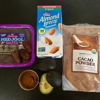 The following ingredients appear against a black table top: (1) Fancy Medjool dates; (2) Almond Breeze unsweetened original almond milk; (3) HealthWorks cacao powder; (4) two avocados, one cut open to see the green inside; and (5) a small metal bowl containing ground cinnamon.