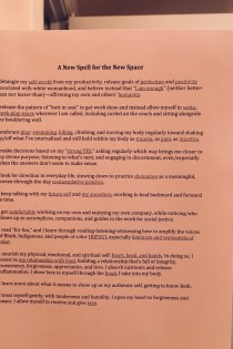 Printed copy of the spell (words that appear in this blog post) taped to a bathroom mirror with a colorful shower curtain showing part of a tree reflected in the mirror. The photo has a pink tint.