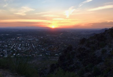 Photo of the sunset over Phoenix, Arizona: the orange sun centered and orange, yellow, and pink colors stretch outward to the photo's edge. The photo is framed by a hillside in the bottom and lower right. The city stretches out from the hillside to the horizon, where the sunset begins.