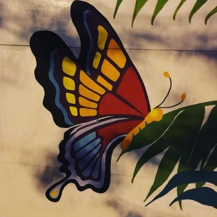 Image of a colorful butterfly (red, orange, yellow, blue, purple, and black) perched on green leaves. This image is painted onto white wooden planks with smudges of grey giving the photo a shadowy quality.