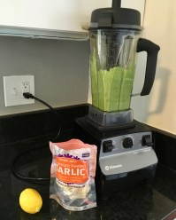 A green sauce appears in a Vitamix (high-powered blender) with peeled garlic and a full lemon sitting nearby, ready to be added if any additional flavors are desired.