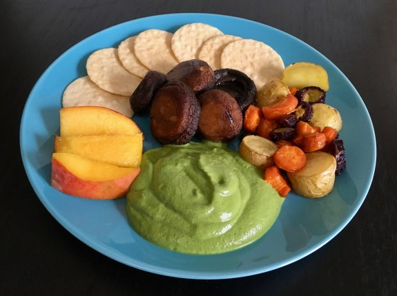 On a blue plate appears a large serving of green pesto sauce (in the front) with sliced peaches, rice crackers, roasted mushrooms, and a mix of orange and purple carrots and yellow-white potatoes.