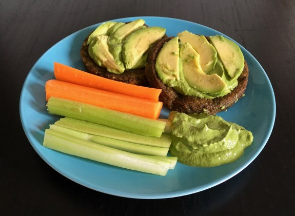 Two veggie burgers topped with slices of avocado appear on a blue plate, along with carrot and celery sticks and pesto dipping sauce.