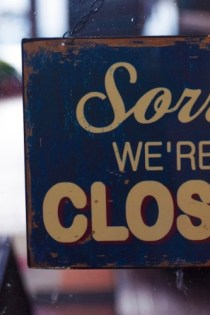 "This image shows a sign that reads ""Sorry we're closed"" against a dark and shadowy background."