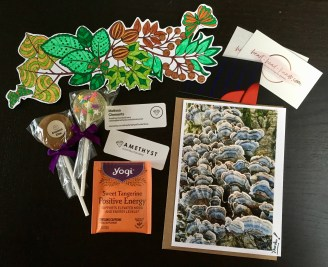 "Sample thank-you package contents, including a homemade card and bookmark, tea for ""positive energy,"" and vegan + gluten-free candy from Amethyst Confections."