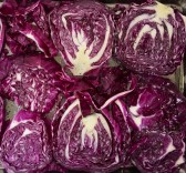 Here the red cabbage slices are positioned side-by-side on a baking sheet and covered with oil, salt, and pepper. They are ready for roasting.