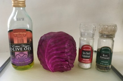 This photo shows four ingredients against a white wall and a white cutting board. From left to right, these are oil, red cabbage, salt, and pepper.