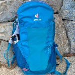 Here a teal-blue hiking backpack (lighter day-pack with thermos visible) sits against a stone bench.