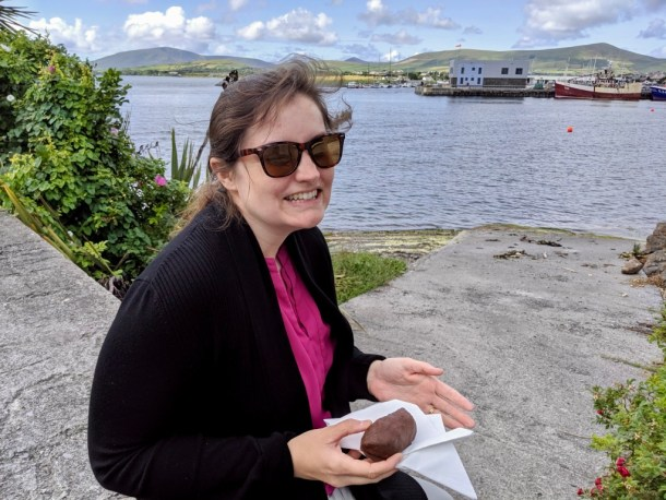 Beth eating a vegan mounds bar (chocolate and coconut) at the Dingle Harbor in County Kerry, Ireland.