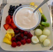 Vegan coconut yogurt surrounded by berries, mango, pineapple, kiwi, and melon.
