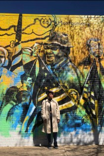 Photo of Alexa Eason standing against a mural on the Civil Rights Trail in Montgomery, Alabama.