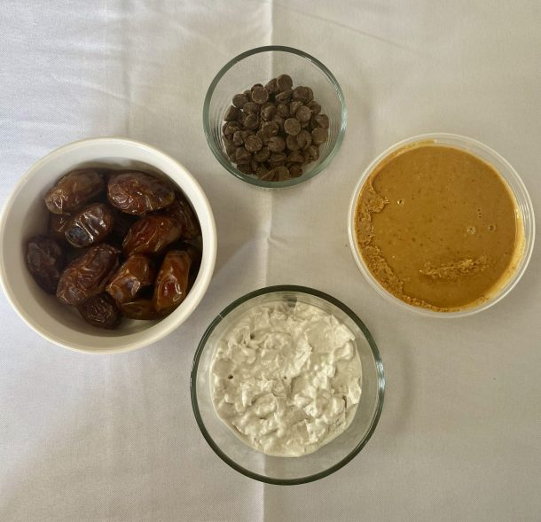 Ingredients for vegan stuffed dates (moving clockwise): fresh Medjool dates, semi-sweet chocolate chips, peanut butter, and coconut cream.