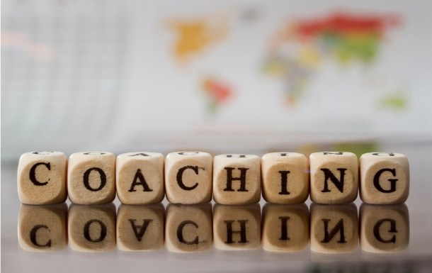 The word coaching is spelled out of scrabble blocks in the foreground with a faded image of a world map in the background.