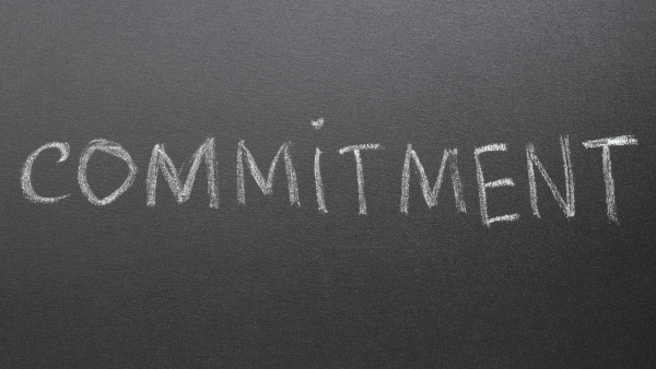 "This image shows the word ""commitment"" written in white chalk on a grayish blackboard."