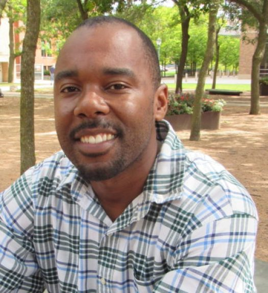 This photo shows Cedric D. Burrows, Ph.D., wearing a patterned shirt and sitting in a park with trees and buildings in the background.