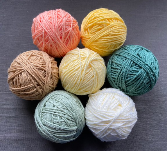 seven balls of yarn (in shades of yellow, orange, cream, green, and teal) for my current crochet project