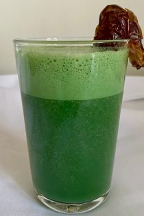 This image shows the spirulina shake (a bright green smoothie) in a clear glass, a brown date attached to the rim, against a white tablecloth.
