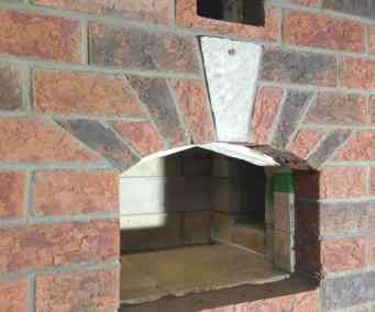 jack arch over bake oven door in this double-bell masonry heater