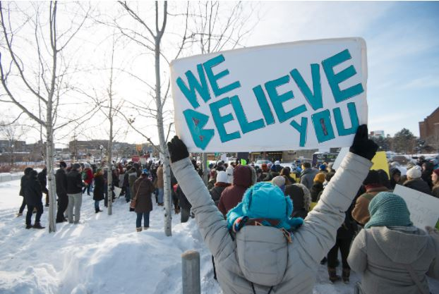 """Person holding sign that says """"We Believe You"""" with people marching in the background."""