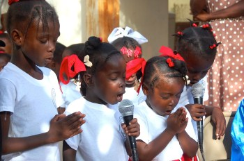 Children praying together in Haiti