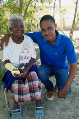 Moise, the leader of Heartline's Discipleship and Community Outreach Team in Haiti, kneels next to Talita, an elderly Haitian friend