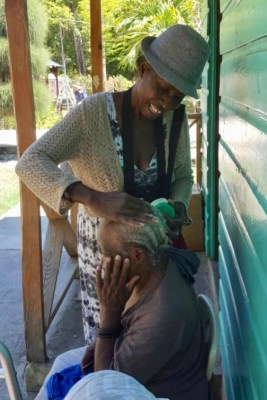 Haitian woman volunteers with Heartline Ministries Haiti to braid the hair of an elderly woman
