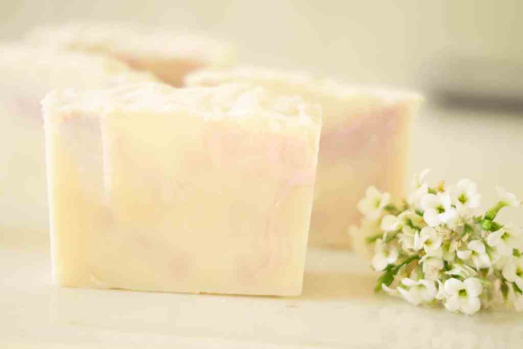 mango soap bar standing upright next to white flower