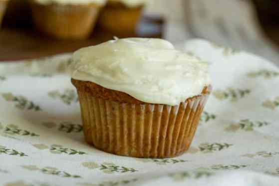 sourdough carrot cupcake with cream cheese frosting resting on on towel