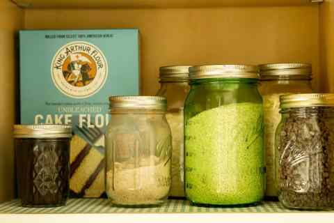 mason jars with homemade pantry goods in cabinet