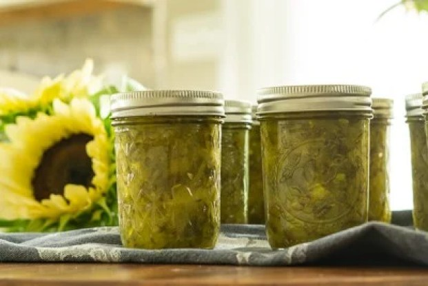 six half pint jars of dill pickle relish on wooden surface with white nite sunflowers in background