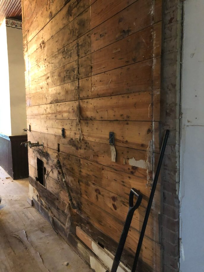 "This is one of the few wood walls downstairs. The crew is currently getting rid of the ""kitchen"" along this wall."