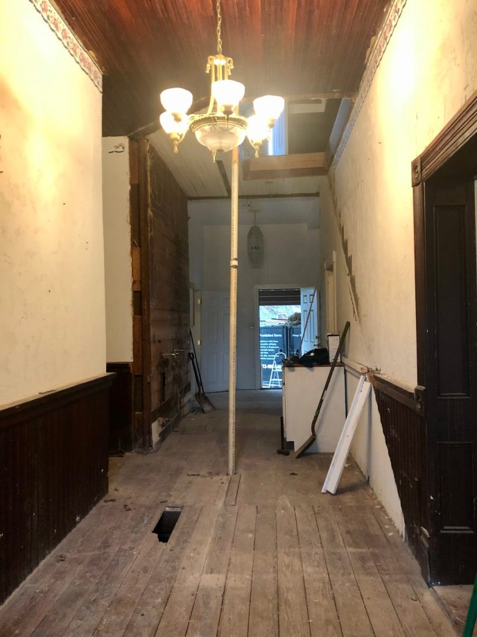 In the entry hallway is a hole in the floor that had been covered up, and a fascinating pipe. We do not plan to hold pole dancing classes in here.