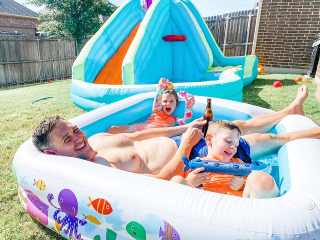 two kids and their dad in an inflatable pool in their backyard